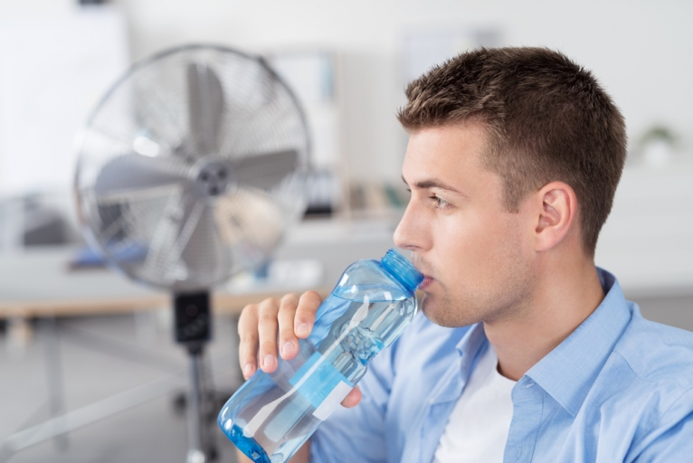 Close up Handsome Young Man Inside the Office, Drinking a Bottle Water While Looking Into Distance.